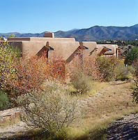 A contemporary adobe house near Santa Fe, New Mexico has been designed to blend seamlessly with the scrub landscape outside