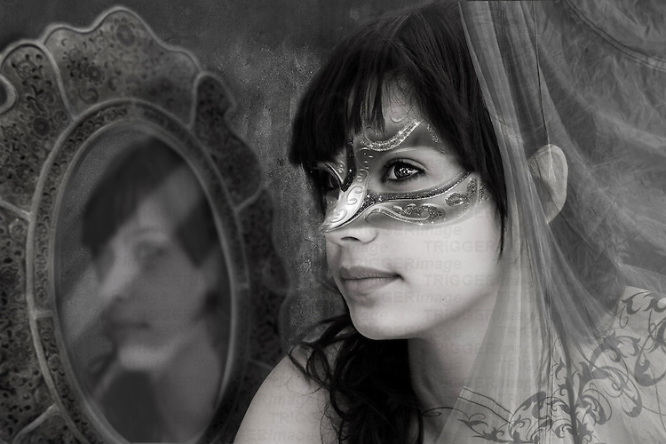 fantasy image of a girl wearing a mask sitting by a mirror