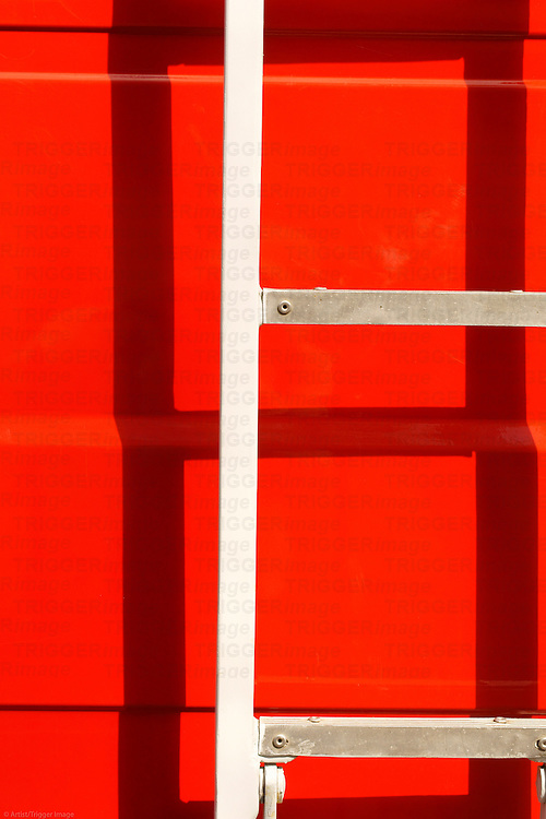 The closeup of a body of a fire truck in the sunshine with a ladder, which casts a shadow.