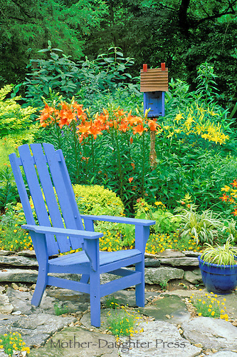 Colorful summer sun garden scene with painted matching birdhouse and wooden chair contrasting with orange and yellow floral garden