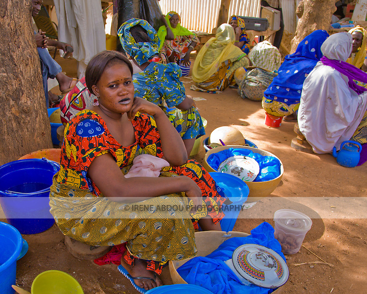 "A woman sells ""cobbal"" and milk (balls of boiled and pounded millet eaten with milk and sugar like a cereal) at the market in Torodi, Niger, where each Friday, hundreds of people converge from surrounding villages. Cobbal is made by pounding millet, boiling it, pounding it again with a small amount of water, then rolling it into a ball..While this woman may be starting small, her ambition is to save enough money to one day start her own ""restaurant."""