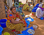"""A woman sells """"cobbal"""" and milk (balls of boiled and pounded millet eaten with milk and sugar like a cereal) at the market in Torodi, Niger, where each Friday, hundreds of people converge from surrounding villages. Cobbal is made by pounding millet, boiling it, pounding it again with a small amount of water, then rolling it into a ball..While this woman may be starting small, her ambition is to save enough money to one day start her own """"restaurant."""""""