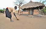 Rosa Lonyako, 10, sweeps around her family's home early in the morning in Pisak, a small village in Central Equatoria State in Southern Sudan.
