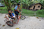 """Pedal power gets these boys to school in Nalapaan, one of seven villages near Pikit which has declared itself a """"space for peace."""" An initiative of the Immaculate Conception Parish in Pikit, the spaces for peace are villages where residents have told both the Moro Islamic Liberation Front and the Philippine military to desist from activity within the community. Residents also studied peacebuilding and conflict resolution,  and have made special efforts to increase interfaith dialogue and harmony."""
