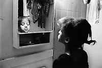 "USA. New York City. Spanish Harlem. Sala looks at herself in the mirror in the bathroom. The Puerto Rican family lives below the poverty line and receives public assistance (AFDC, Home Relief, Supplemental Security Income and Medicaid). The family resides in units managed by the New York City Housing Authority (NYCHA) which provides housing for low income residents. NYCHA administers rental apartments in facilities, popularly known as ""projects"". Spanish Harlem, also known as El Barrio and East Harlem, is a low income neighborhood in Harlem area. Spanish Harlem is one of the largest predominantly Latino communities in New York City. 4.04.86 © 1986 Didier Ruef"