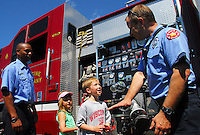 Patrick Hayes and his sister, Sophia, talk with Madison firefighters Steve Dahlgren (right) and Jason Suttle (left) at emergency response demonstrations at All-Star Sunday at Warner Park on Sunday in Madison