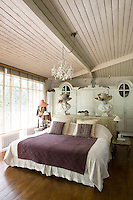 In the large, feminine bedroom hats by Phillippe Model are perched on marble busts on top of a cupboard behind the bed