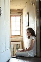 Young woman seated in doorway looking down
