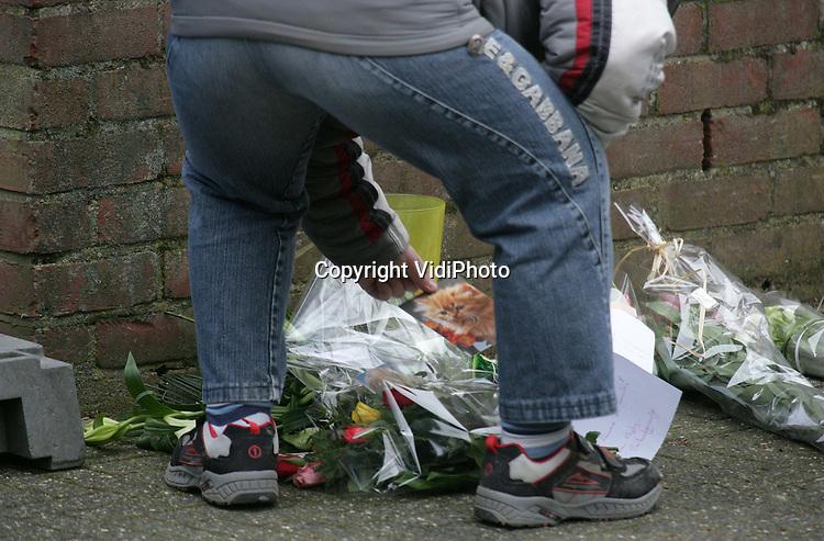 Foto: VidiPhoto..HUISSEN - Buurtbewoners hebben woensdag bloemen, tekeningen en kaarten neergelegd voor de blauwe schermen die nog steeds rond de plek staan waar dinsdagavond in een woning aan de Kuunskop vier lichamen werden gevonden. Woensdag werd ook een buurtonderzoek gehouden door de politie. De politie wil nog steeds niets zeggen over de identiteit van de slachtoffers en de toedracht van het drama.