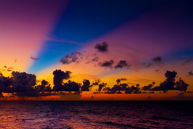 Vibrant rays of light streak through distant clouds over the Caribbean waters at sunset. (Photo by Jeff Speer © www.JeffSpeer.com)