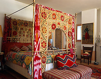 An antique wrought iron four-poster bed has colourful suzanis and lengths of tie-dye fabric as bed hangings