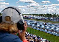 Aug 21, 2016; Brainerd, MN, USA; A fan watches as NHRA top fuel dragster driver Brittany Force (left) races alongside Shawn Langdon during the Lucas Oil Nationals at Brainerd International Raceway. Mandatory Credit: Mark J. Rebilas-USA TODAY Sports