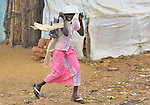 A woman runs through the rain in the Khamsadegaig camp for internally displaced families, where victims of the conflict in Sudan's Darfur region have taken refuge.