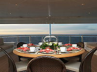 An intimate dining table is laid for breakfast on a private terrace aft with views over the sea