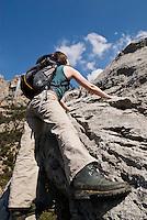 Young adult female hiker climbs on limestone rocks at Gorge du Verdon, France