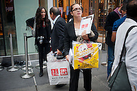 Customers with their purchases outside the grand opening of the Uniqlo Flagship store on Fifth Avenue in New York on Friday, October 14, 2011.  The store is a staggering 89,000 square feet on multiple levels and is Fast Retailing's second store in the United States with a third opening next week in the Herald Square shopping district. The largest store on Fifth Avenue filled to the brim with affordable clothing it competes with stalwarts such as the Gap and Zara which are in the immediate proximity. Fast Retailing plans on opening 200 to 300 stores worldwide until 2020 and currently has 1000 stores. (© Richard B. Levine)