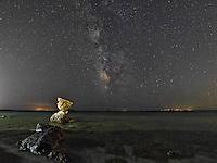 Rocky coast under the Milky Way in Andros, Greece