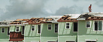 A person walks along apartment roofs on Navarre Beach, Florida as the Governor toured the area after Hurricane Opal.  Hurricane Opal impacted the Florida panhandle as a category three storm when it came ashore near Pensacola, Florida October 4, 1995.  It was the strongest hurricane of the 1995 season and killed 63 people, 13 in the United States.  Hurricane Opal's name was retired the following year.