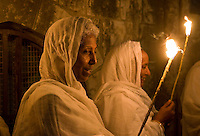 JERUSALEM - APRIL 14 : Ethiopian Orthodox worshipers hold candles during the Holy fire ceremony at the Ethiopian section of the Holy Sepulcher in Jerusalm Israel on April 14 2012