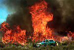 """(05-8-02) SAN BERNARDINO--METRO--A fire fighter near the SUV uses a flare to set backfires to use up what fire officials term, """"fuel"""" in order to prevent the recurence of flareups, behind Cal State San Bernardino, Wednesday. STAFF PHOTO BY Rodrigo Peña."""