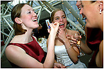 A bride and friends share a laugh about an old photograph during the wedding reception.