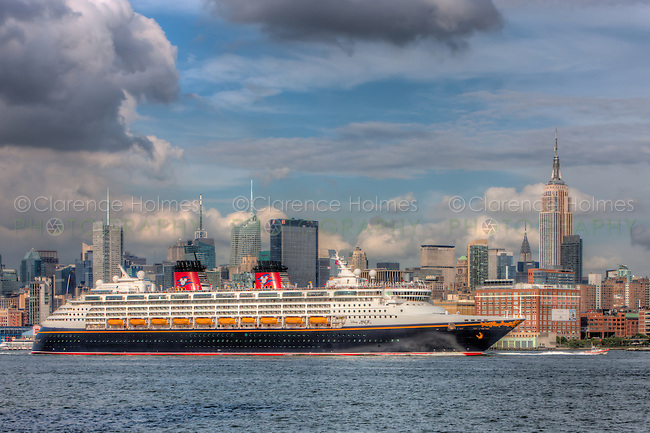 Disney Cruise Line cruise ship Disney Magic heads south on the Hudson River past the New York City skyline, under threatening skies, after departing the New York Passenger Ship Terminal on the west side of Manhattan.