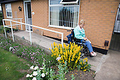Woman wheelchair user leaving her house using a concrete ramp. MR