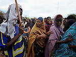 A man with a cane keeps women in line as they wait for food to be distributed at the reception center of the Dagahaley refugee camp, part of the Dadaab refugee complex in northeastern Kenya.