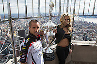 """New York, USA. 23 April 2014.  Supercross motorcycle racer Mike Alessi and """"Miss Supercross"""" Dianna Dahlgren hold the trophy as they promote their motorcycle race during a visit to the Empire State Building in New York. Photo by Eduardo Munoz Alvarez/VIEWpress"""