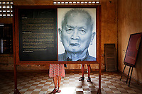 """Tourists are seen behind a portrait of former Khmer Rouge leader """"Brother Number two"""" Nuon Chea as they read about him at the former notorious Tuol Sleng prison that is now the Genocide Museum in Phnom Penh August 5, 2014. Cambodia's young population is very aware of its grim history, with almost every family suffering losses. Most Cambodians still want justice and to see the U.N.-backed court find the recalcitrant Nuon Chea, Pol Pot's right-hand man, and ex-President Khieu Samphan, guilty of crimes against humanity, but the court has been mired in disputes, resignations, funding shortages and accusations of political interference and has to date delivered just one verdict. The court will deliver verdicts for Noun Chea and Khieu Samphan on August 7, 2014. Picture taken August 5, 2014. REUTERS/Damir Sagolj (CAMBODIA)"""