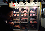 A buyer walks past a refrigerator containing pieces of tuna fish at Tsukiji fish market in Tokyo on Oct. 31, 2008. .Photographer: Robert Gilhooly
