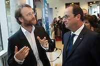 French President Francois Hollande listens to a scientist from Universite Laval in Quebec city, Tuesday November 4, 2014.