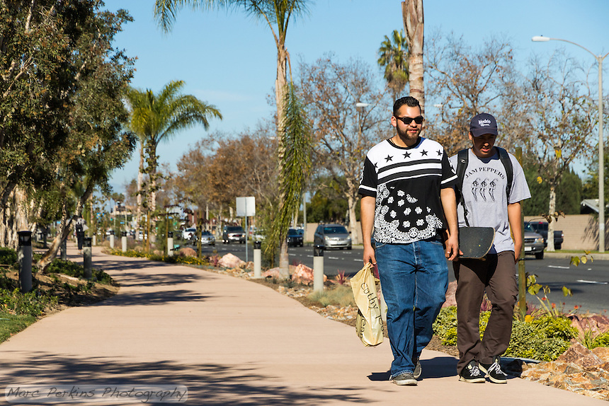 Two young men walk towards the camera carrying bags and smiling along the Harbor Boulevard Cornerstone Bike Trail in Costa Mesa, California under a clear blue sky.  The two men are both carrying items, and are clearly just casually walking along the relaxing trail; a few cars are visible on Harbor Blvd. in the background, but their blurred nature and hardscaping in between them and the people makes the cars not seem threatening.  The landscaping of the path, including a diversity of plants and rocks, can be seen behind the people.  The landscape architecture work on the project was done by David Volz Design.