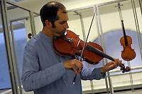 """Musicista mentre prova uno strumento. Musician tests a violin..Consorzio Liutai """"Antonio Stradivari"""". The Consortium of Violinmakers."""