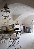 Rough stone walls and bleached antique wood cupboards create a rustic atmosphere in the kitchen