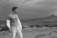 man with a great body removing his shirt and looking at the New Mexico landscape
