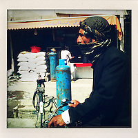 A man in a head scarf rides a bicycle along a street, passing a large gas cylinder outside a shop.