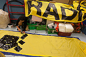 Motoko Tatsumi painting banners on board the Greenpeace ship Rainbow Warrior, as it transits northwards to Fukushima, Japan, on Monday 25th April 2011.
