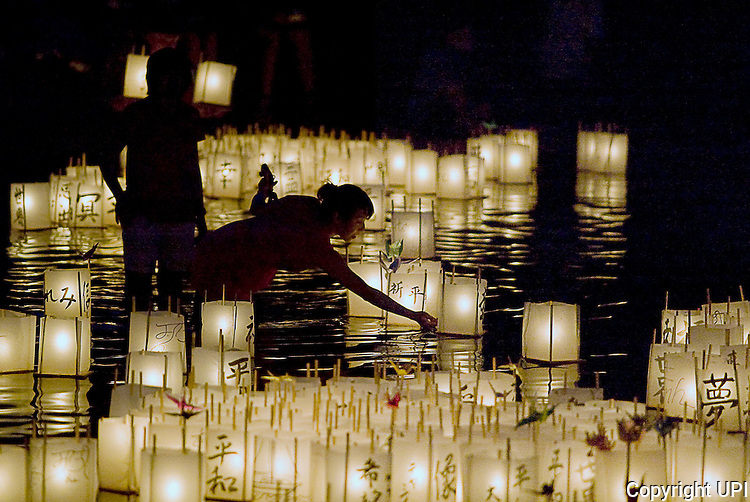 A volunteer is surrounded by lighted lanterns as they float in Green Lake during the From Hiroshima to Hope, an annual peace event held in Seattle August 6, 2012. The lantern floating ceremony is a Japanese Buddhist ritual, in which lanterns representing the souls of the dead are floated out to sea. The ceremony is re-enacted each year at this time in Hiroshima and Nagasaki and other cities throughout the world in remembrance of the atomic bomb victims. (UPI Photo/Jim Bryant)).