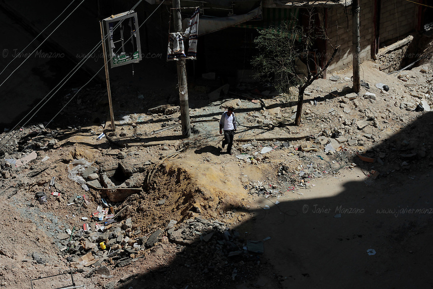 A man walks next to the crater left by a bomb dropped by a Syrian Jet in the opposition held neighborhood of Sha'ar in Aleppo.