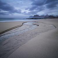 A small river runs through the sand at Storsandnes beach, Flakstadøy, Lofoten Islands, Norway
