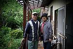 Katsurao, May 30 2011 - .(eng) Kunio Abe and his wife Minako pictured in front of their house. After having lived in the suburbs of Tokyo until they retired, they settle in this countryside village 15 years ago to cultivate their own organic vegetables...(fr) Kunio  et sa femme Minako Abe posent devant leur maison. Après avoir vécu dans la banlieue de Tokyo jusqu'a leur retraite, le couple est venu s'installer a la campagne il y a 15 ans pour cultiver des légumes bio. .M. Abe s'excuse pour les mauvaises herbes qui poussent dans le chemin d'accès a la maison.