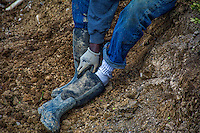 Workers puts on waterproof boots before stepping into mud at the State And Schrock road construction site.