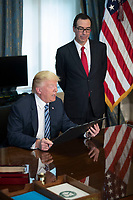 US President Donald J. Trump (L), with Secretary of Treasury Steven Mnuchin (R) reads a financial services Executive Order prior to signing during a ceremony in the US Treasury Department building in Washington, DC, USA, 21 April 2017. President Trump is making his first visit to the Treasury Department for a memorandum signing ceremony with Secretary Mnuchin.<br /> Credit: Shawn Thew / Pool via CNP /MediaPunch