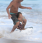 Dad teaches his son how to skim board along Sandy Beach in Hawaii.