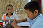 Eleven-year old Juan Lopez writes in Braille as his teacher, Betsy Jimenez, dictates during class at a school in Zipolite, a town in Oaxaca, Mexico. Juan is blind, and yet refuses to be sidelined. He rides his bike, for example, with his sister's help. She perches on the back and signals him which way to steer by pinching his shoulder. If she pinches his right shoulder, for example, he goes right. The harder the pinch, the sharper the turn.