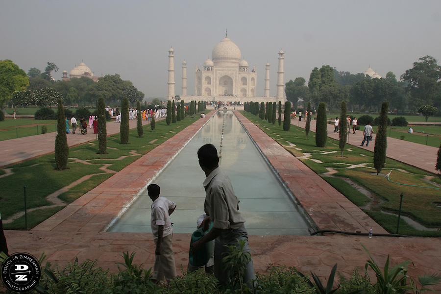 An employee waters plants on the grounds of the Taj Mahal in Agra, India. The Taj Mahal is regarded by many as one of the eight modern wonders of the world. The mausoleum was built by Mughal Emperor Shah Jahan to immortalize his love for his wife Mumtaz Mahal.  Construction for the Taj Mahal began in 1631 and completed in 1653.  Photograph by Douglas ZImmerman