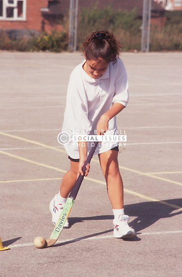 Secondary school girl playing hockey,