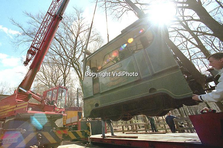 Foto: VidiPhoto..ARNHEM - Met behulp van een mega-hijskraan en drie diepladers is vrijdag een historische stoomtram overgebracht van het Openluchtmuseum in Arnhem .naar het Nationaal Spoorwegmuseum in Valkenburg (ZH). De 27 meter lange combinatie van een locomotief en twee wagons nam in Arnhem te veel ruimte in beslag. Bovendien ging het om een smalspoorstoomtram, terwijl er in het Openluchtmuseum gebruik wordt gemaakt van  zogenaamd normaalspoor. Er kon dus nooit mee gereden worden. Foto: De stoomlocomotief wordt omhoog gehesen.