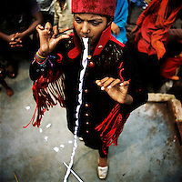 Nine year old Tarveena the Magician performs her paper eating trick in the Kathputli Colony. Located in northwest Delhi, Kathputli is inhabited by approximately 2,000 performing artists, practicing traditional art forms such as marionette puppetry, juggling, magic, acrobatics, dance and music. Many have travelled all over the world showcasing their abilities, but they still choose to remain living in this slum, which is one of the most impoverished in the city.